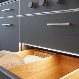 Inredning av ett modernt avskilt, mellanstort grå grått l-kök, med en integrerad diskho, släta luckor, grå skåp, bänkskiva i kvarts, flerfärgad stänkskydd, stänkskydd i porslinskakel, integrerade vitvaror, mellanmörkt trägolv, en köksö och svart golv
