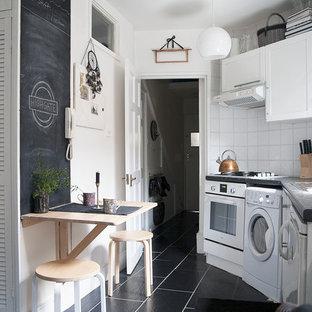 ロンドンの小さいエクレクティックスタイルのおしゃれなキッチン (シングルシンク、フラットパネル扉のキャビネット、白いキャビネット、ラミネートカウンター、白いキッチンパネル、セラミックタイルのキッチンパネル、白い調理設備、セラミックタイルの床、アイランドなし、黒い床) の写真