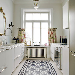 Photo of a classic galley kitchen in London with a submerged sink, flat-panel cabinets and white cabinets.