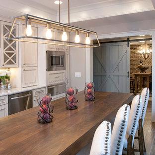 アトランタの大きいトランジショナルスタイルのおしゃれなキッチン (アンダーカウンターシンク、落し込みパネル扉のキャビネット、ベージュのキャビネット、茶色いキッチンパネル、シルバーの調理設備の、濃色無垢フローリング、大理石カウンター、レンガのキッチンパネル、茶色い床、白いキッチンカウンター) の写真