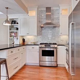 На фото: п-образная кухня-гостиная среднего размера в классическом стиле с врезной раковиной, фасадами с утопленной филенкой, белыми фасадами, столешницей из кварцита, серым фартуком, фартуком из каменной плитки, техникой из нержавеющей стали, полом из бамбука и полуостровом