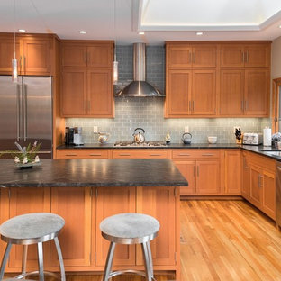 Inspiration for a contemporary l-shaped kitchen in New York with an undermount sink, shaker cabinets, light wood cabinets, granite benchtops, grey splashback, glass tile splashback, stainless steel appliances, with island and medium hardwood floors.