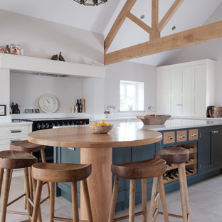 Photo of a large farmhouse kitchen in Cheshire with quartz worktops, porcelain flooring, an island, white worktops, a belfast sink, shaker cabinets, white cabinets, black appliances and beige floors.