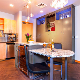 Mid-sized contemporary eat-in kitchen designs - Mid-sized trendy u-shaped medium tone wood floor and brown floor eat-in kitchen photo in Portland with flat-panel cabinets, gray cabinets, granite countertops, beige backsplash, glass tile backsplash, stainless steel appliances and an island