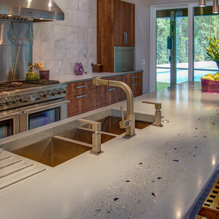 Photo of a large contemporary l-shaped open plan kitchen in Tampa with a triple-bowl sink, flat-panel cabinets, medium wood cabinets, concrete benchtops, stone tile splashback, stainless steel appliances, porcelain floors and with island.