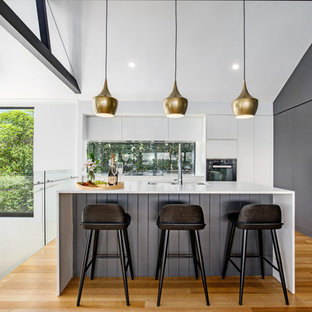 Mid-sized contemporary l-shaped open plan kitchen in Sunshine Coast with an undermount sink, flat-panel cabinets, quartz benchtops, window splashback, with island, white benchtop, white cabinets, panelled appliances, medium hardwood floors and brown floor.