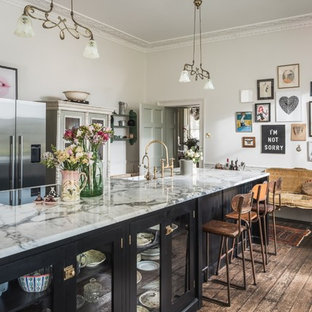 Vintage enclosed kitchen in Other with glass-front cabinets, black cabinets, dark hardwood flooring, an island, brown floors, grey worktops and a belfast sink.