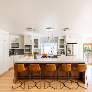 Mittelgroße Mid-Century Küche in L-Form mit Unterbauwaschbecken, flächenbündigen Schrankfronten, weißen Schränken, Quarzit-Arbeitsplatte, Küchenrückwand in Grau, Rückwand aus Marmor, Küchengeräten aus Edelstahl, hellem Holzboden, Kücheninsel und beigem Boden in Los Angeles