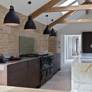 Kitchen - farmhouse kitchen idea in London with flat-panel cabinets, dark wood cabinets, stainless steel countertops, glass sheet backsplash and an island