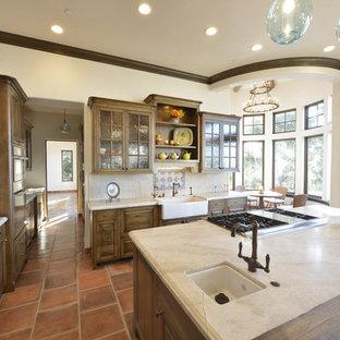 サンフランシスコの大きいトラディショナルスタイルのおしゃれなキッチン (エプロンフロントシンク、レイズドパネル扉のキャビネット、濃色木目調キャビネット、珪岩カウンター、ベージュキッチンパネル、セラミックタイルのキッチンパネル、シルバーの調理設備、テラコッタタイルの床、赤い床、ベージュのキッチンカウンター) の写真