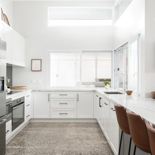 This is an example of a contemporary u-shaped kitchen in Sydney with an undermount sink, shaker cabinets, white cabinets, stainless steel appliances, a peninsula, grey floor and white benchtop.