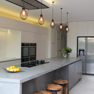 Inspiration for a contemporary galley open plan kitchen in London with flat-panel cabinets, white cabinets, concrete benchtops and stainless steel appliances.