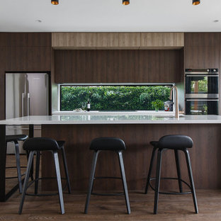 This is an example of a contemporary galley kitchen in Melbourne with an undermount sink, flat-panel cabinets, dark wood cabinets, window splashback, stainless steel appliances, dark hardwood floors, with island, brown floor and white benchtop.