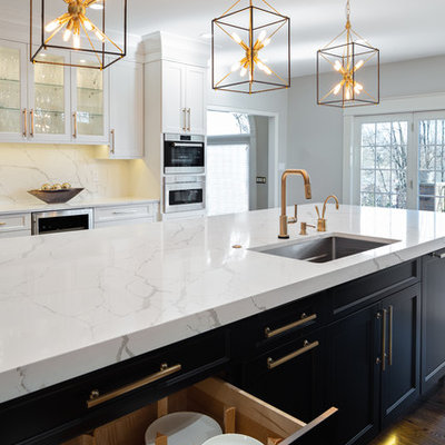 Large transitional u-shaped dark wood floor and brown floor kitchen photo in Other with an undermount sink, flat-panel cabinets, white cabinets, quartz countertops, white backsplash, stone slab backsplash, stainless steel appliances, an island and white countertops