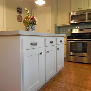 Small coastal l-shaped kitchen/diner in San Francisco with a submerged sink, shaker cabinets, white cabinets, recycled glass countertops, blue splashback, metro tiled splashback, stainless steel appliances, medium hardwood flooring and an island.