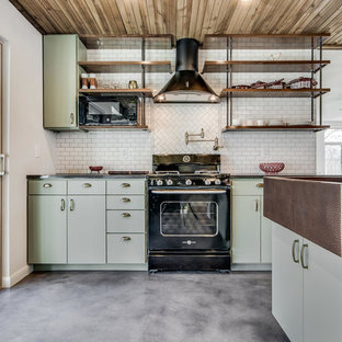 Industrial kitchen remodeling - Urban l-shaped concrete floor and gray floor kitchen photo in Austin with a farmhouse sink, flat-panel cabinets, green cabinets, wood countertops, white backsplash and black appliances