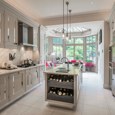 Mid-sized transitional galley gray floor eat-in kitchen photo in London with an undermount sink, recessed-panel cabinets, gray cabinets, white backsplash, marble backsplash and an island