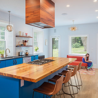Contemporary kitchen ideas - Inspiration for a contemporary galley light wood floor kitchen remodel in Philadelphia with an undermount sink, flat-panel cabinets, blue cabinets, white backsplash, subway tile backsplash, stainless steel appliances and an island