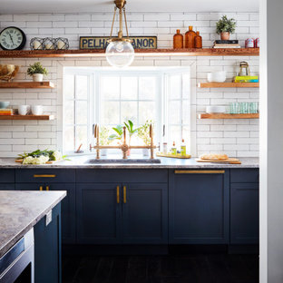 Bild på ett stort lantligt grå grått kök, med en undermonterad diskho, skåp i shakerstil, blå skåp, vitt stänkskydd, stänkskydd i tunnelbanekakel, färgglada vitvaror, mörkt trägolv, en köksö och svart golv
