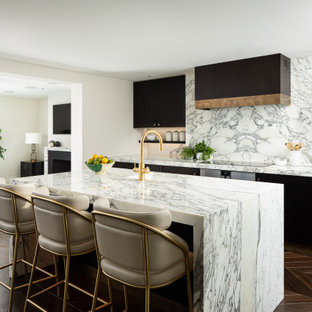 This is an example of a medium sized contemporary galley kitchen/diner in London with a built-in sink, flat-panel cabinets, dark wood cabinets, marble worktops, white splashback, marble splashback, stainless steel appliances, dark hardwood flooring, an island, brown floors and white worktops.