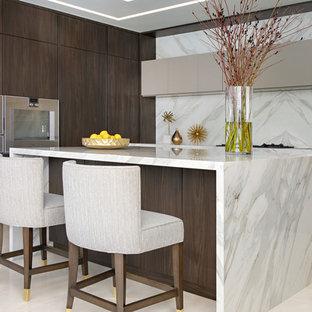 Idéer för funkis grått u-kök, med släta luckor, skåp i mörkt trä, grått stänkskydd, integrerade vitvaror, en köksö och beiget golv