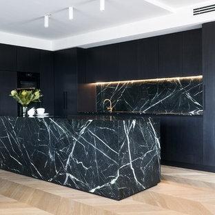 Photo of a contemporary kitchen in Sydney with flat-panel cabinets, black cabinets, black splashback, stone slab splashback, light hardwood floors, with island, beige floor, black benchtop and panelled appliances.