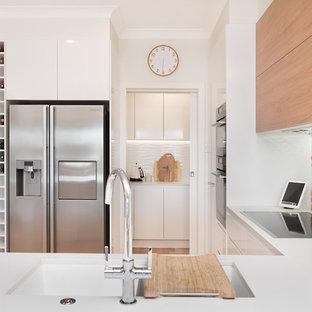 This is an example of a beach style u-shaped kitchen in Townsville with an undermount sink, flat-panel cabinets, white cabinets, white splashback, stainless steel appliances and white benchtop.