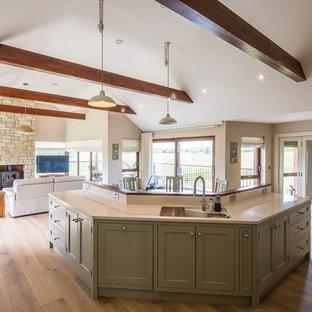 他の地域の中サイズのカントリー風おしゃれなキッチン (一体型シンク、シェーカースタイル扉のキャビネット、緑のキャビネット、クオーツストーンカウンター、白いキッチンパネル、パネルと同色の調理設備、淡色無垢フローリング、茶色い床、白いキッチンカウンター) の写真