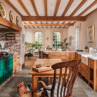 サセックスの大きいトラディショナルスタイルのおしゃれなキッチン (エプロンフロントシンク、中間色木目調キャビネット、大理石カウンター、カラー調理設備、グレーの床、白いキッチンカウンター、シェーカースタイル扉のキャビネット、赤いキッチンパネル、レンガのキッチンパネル) の写真