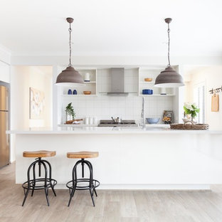 Inspiration for a mid-sized transitional galley kitchen in Melbourne with white splashback, ceramic splashback, light hardwood floors, with island, brown floor, white benchtop, an undermount sink, open cabinets, white cabinets and stainless steel appliances.