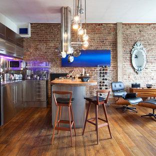 ロンドンの大きいインダストリアルスタイルのおしゃれなキッチン (フラットパネル扉のキャビネット、ステンレスキャビネット、ステンレスカウンター、シルバーの調理設備の、無垢フローリング、ドロップインシンク) の写真