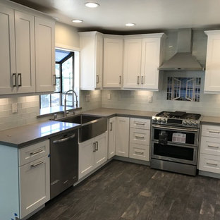 This is an example of a mid-sized contemporary u-shaped eat-in kitchen in Los Angeles with a farmhouse sink, shaker cabinets, white cabinets, quartzite benchtops, red splashback, glass tile splashback, stainless steel appliances, ceramic floors, no island, brown floor and grey benchtop.
