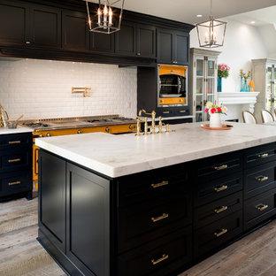 Große Klassische Wohnküche mit Landhausspüle, blauen Schränken, Marmor-Arbeitsplatte, Küchenrückwand in Weiß, Rückwand aus Metrofliesen, hellem Holzboden, Schrankfronten im Shaker-Stil, bunten Elektrogeräten und zwei Kücheninseln in Charlotte