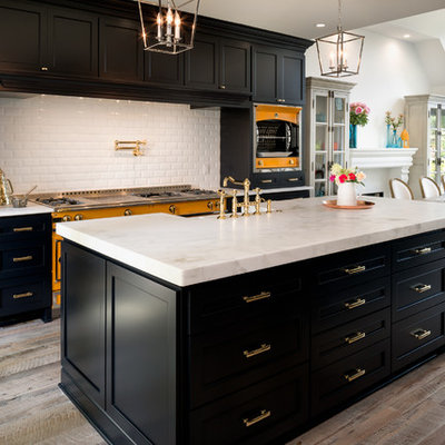 Example of a large transitional light wood floor eat-in kitchen design in Charlotte with a farmhouse sink, marble countertops, white backsplash, subway tile backsplash, shaker cabinets, colored appliances and two islands