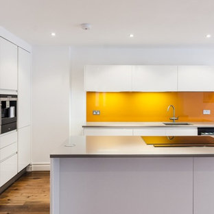 Large modern eat-in kitchen photos - Example of a large minimalist l-shaped medium tone wood floor eat-in kitchen design in London with an undermount sink, flat-panel cabinets, white cabinets, quartzite countertops, orange backsplash, glass sheet backsplash, stainless steel appliances and a peninsula