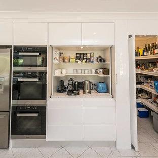 シドニーの広いコンテンポラリースタイルのおしゃれなキッチン (ドロップインシンク、フラットパネル扉のキャビネット、白いキャビネット、クオーツストーンカウンター、白いキッチンパネル、大理石のキッチンパネル、シルバーの調理設備、セラミックタイルの床) の写真