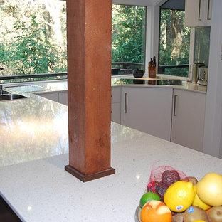 Mid-sized modern kitchen pantry designs - Kitchen pantry - mid-sized modern u-shaped cork floor kitchen pantry idea in Sydney with a drop-in sink, flat-panel cabinets, white cabinets, quartz countertops, green backsplash, glass sheet backsplash, stainless steel appliances and a peninsula