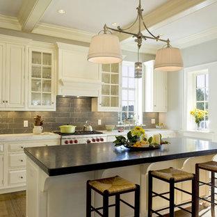 Inspiration pour une cuisine traditionnelle avec un électroménager en acier inoxydable, une crédence grise, des portes de placard blanches, un placard avec porte à panneau surélevé et une crédence en pierre calcaire.