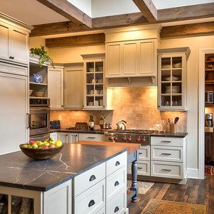 Landhausstil Wohnküche in L-Form mit Speckstein-Arbeitsplatte, zwei Kücheninseln, Schrankfronten im Shaker-Stil, weißen Schränken, Küchenrückwand in Beige, Küchengeräten aus Edelstahl, dunklem Holzboden, Unterbauwaschbecken und Kalk-Rückwand in Sonstige
