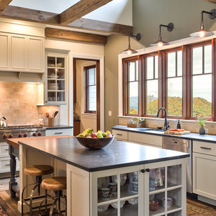 This is an example of a country eat-in kitchen in Other with soapstone benchtops, multiple islands, an undermount sink, white cabinets, stone tile splashback, stainless steel appliances and dark hardwood floors.