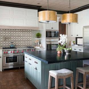 Bild på ett mellanstort vintage kök, med flerfärgad stänkskydd, en rustik diskho, luckor med upphöjd panel, vita skåp, stänkskydd i terrakottakakel, rostfria vitvaror och en köksö