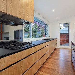 シドニーの大きいコンテンポラリースタイルのおしゃれなキッチン (ドロップインシンク、フラットパネル扉のキャビネット、淡色木目調キャビネット、クオーツストーンカウンター、黒いキッチンパネル、ガラス板のキッチンパネル、シルバーの調理設備の、淡色無垢フローリング、黄色い床) の写真