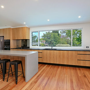 Inspiration for a large contemporary galley kitchen pantry in Sydney with a drop-in sink, flat-panel cabinets, light wood cabinets, quartz benchtops, black splashback, glass sheet splashback, stainless steel appliances, light hardwood floors, a peninsula and yellow floor.