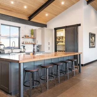 デンバーの大きいラスティックスタイルのおしゃれなキッチン (エプロンフロントシンク、シェーカースタイル扉のキャビネット、白いキッチンパネル、コンクリートの床、茶色い床、グレーのキャビネット、木材カウンター、大理石の床、シルバーの調理設備の、茶色いキッチンカウンター) の写真