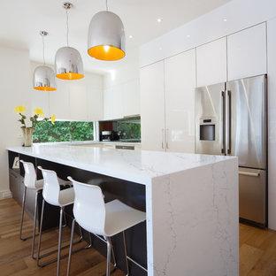 シアトルの中サイズのモダンスタイルのおしゃれなキッチン (アンダーカウンターシンク、フラットパネル扉のキャビネット、白いキャビネット、大理石カウンター、ガラスまたは窓のキッチンパネル、シルバーの調理設備の、無垢フローリング、茶色い床) の写真