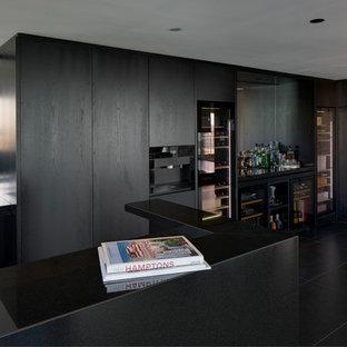 Foto di una grande cucina minimal con lavello a vasca singola, ante lisce, ante nere, top in granito, paraspruzzi a specchio, elettrodomestici neri, pavimento con piastrelle in ceramica, isola e pavimento nero