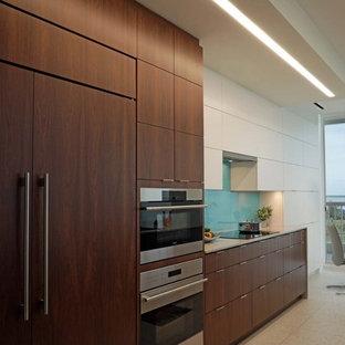 Modelo de cocina comedor contemporánea, de tamaño medio, con fregadero de un seno, armarios con paneles lisos, puertas de armario de madera oscura, encimera de cuarzo compacto, salpicadero de vidrio templado, electrodomésticos con paneles, suelo de terrazo, una isla y suelo blanco