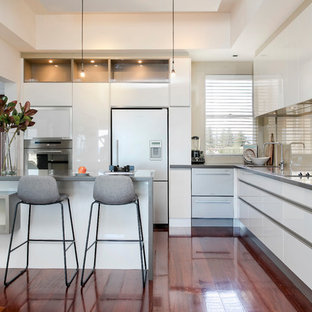 Design ideas for a contemporary l-shaped kitchen in Adelaide with an undermount sink, flat-panel cabinets, white cabinets, beige splashback, glass sheet splashback, white appliances, medium hardwood floors, with island, brown floor and grey benchtop.