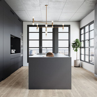 Design ideas for a large contemporary open plan kitchen in Montreal with an undermount sink, flat-panel cabinets, grey cabinets, laminate benchtops, black splashback, glass tile splashback, light hardwood floors, with island, stainless steel appliances and beige floor.