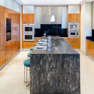 マイアミの大きいビーチスタイルのおしゃれなアイランドキッチン (中間色木目調キャビネット、珪岩カウンター、黒いキッチンパネル、ベージュの床、黒いキッチンカウンター、フラットパネル扉のキャビネット、パネルと同色の調理設備) の写真